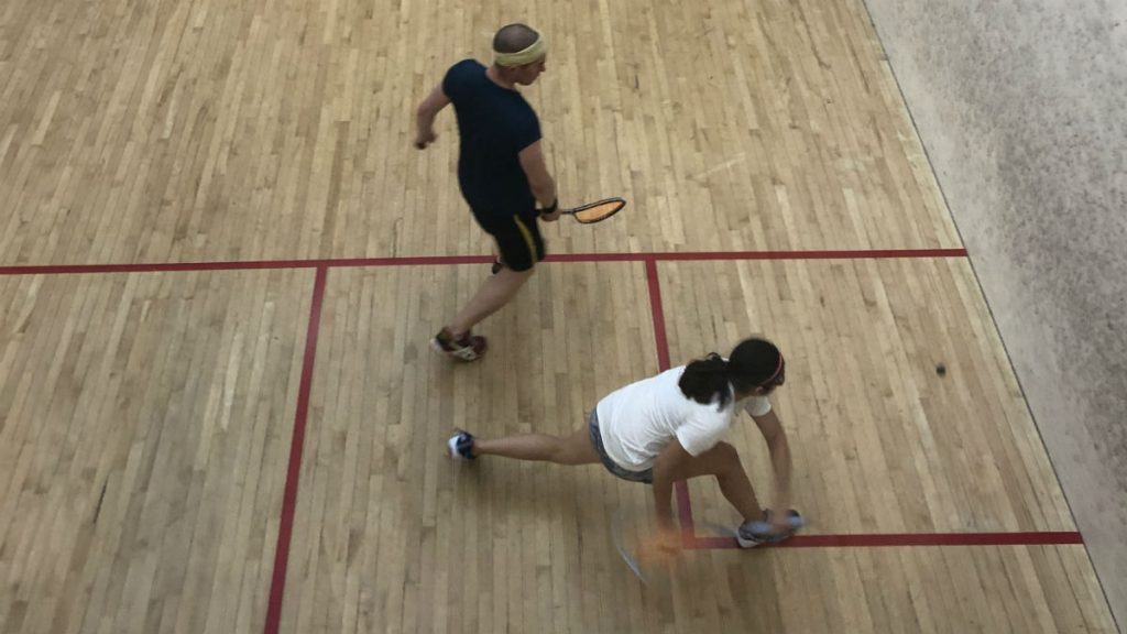 athlete dives to get the ball, racket blurred by the motion and lunging to make the shot.