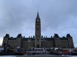 The Centre Block of Parliament, with the Peace Tower at the centre, and construction and fencing in the foreground. The clouds above are dark and grey.