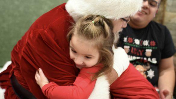 Young girl hugging Santa Claus at a Sensory Santa.