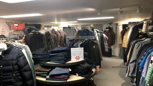 an image of clothes neatly piled in a consignment store