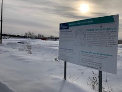 The business building proposal sign for Barrhaven's downtown core located in front of the undeveloped land that is currently covered in snow.