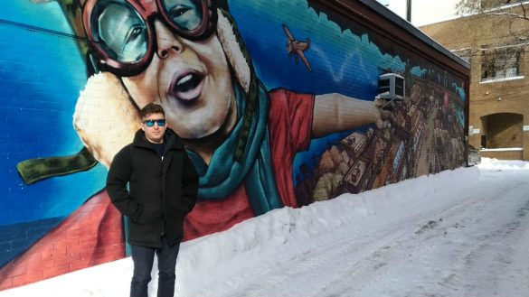 Artist Dan Metcalfe standing in front of a mural he painted of a child flying over the Glebe
