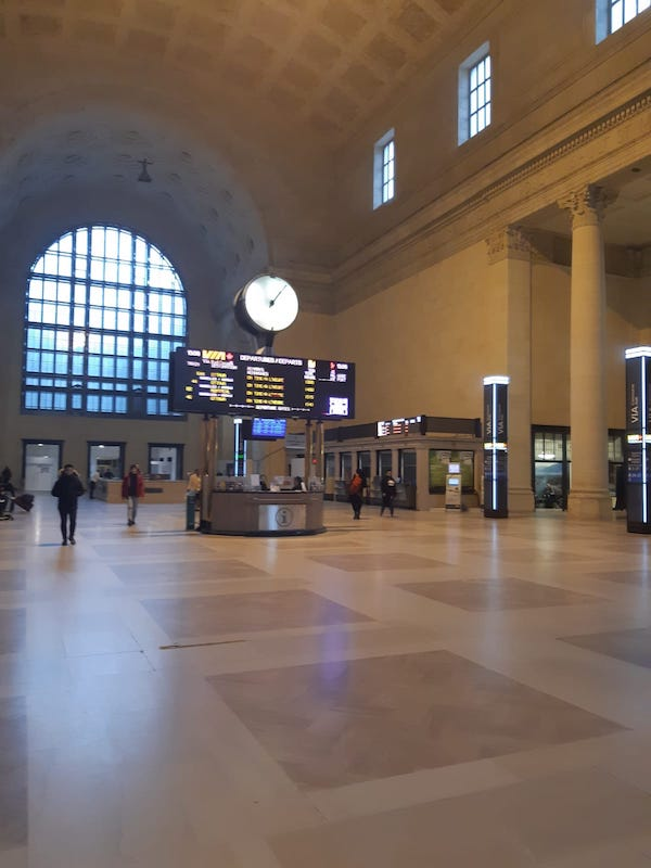 Union station empty. In the centre is the help desk and departure/arrival sign.
