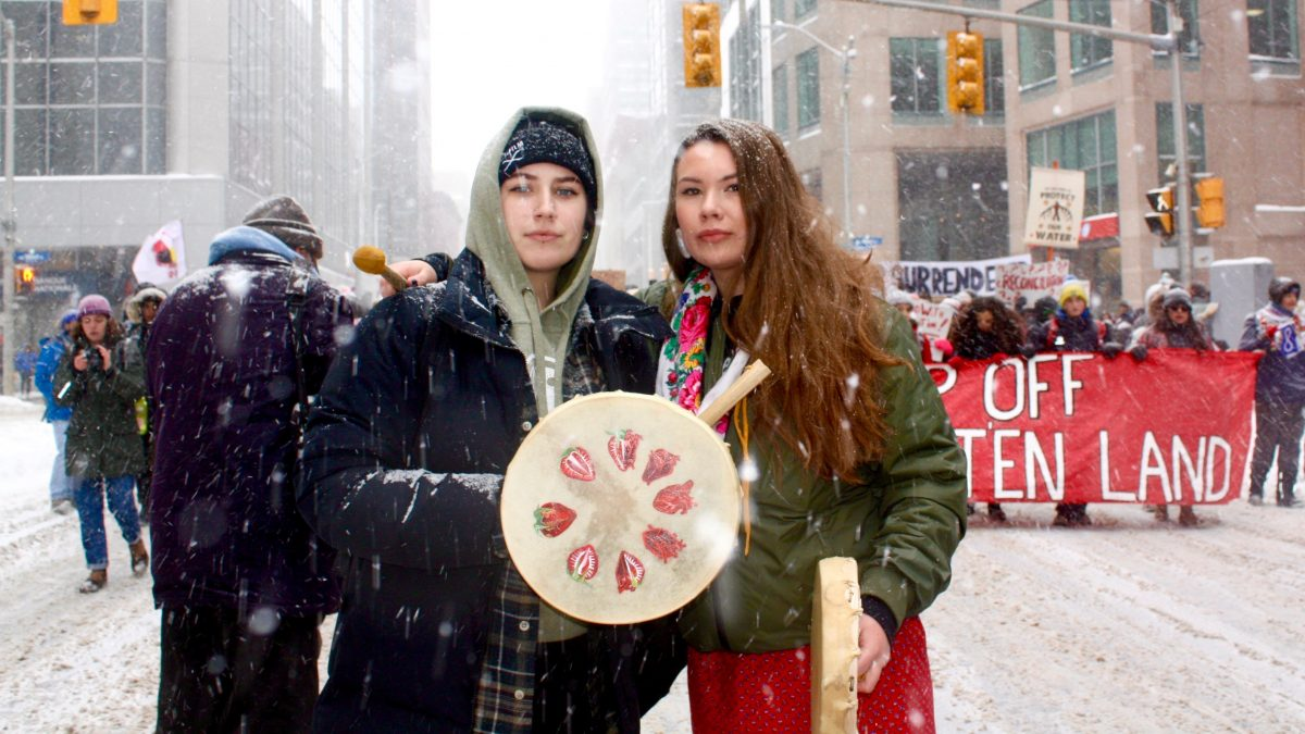 Two Indigneous women holding drums look at the camera, posed with the rally in the backdrop.