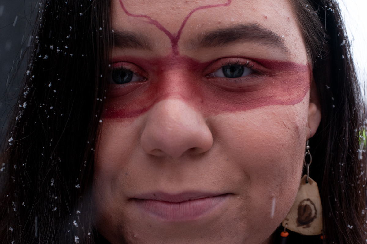Close up of protestors face with red paint across her eyes