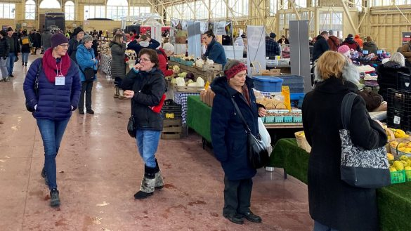 Many people are shopping for food and other goods at a farmers market.