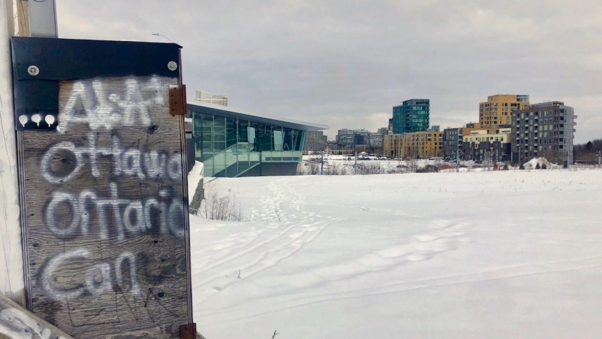 "Large field covered in snow with Pimisi station and the Claridge Homes condo buildings in the background. Wooden box with ""Ottawa, Ontario, Can"" written on it in the foreground."