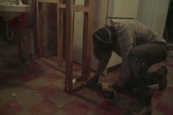 Man using a power tool to cut through wood.