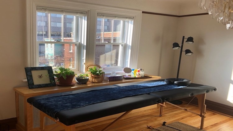 A photo of a massage table by a well-lit window.