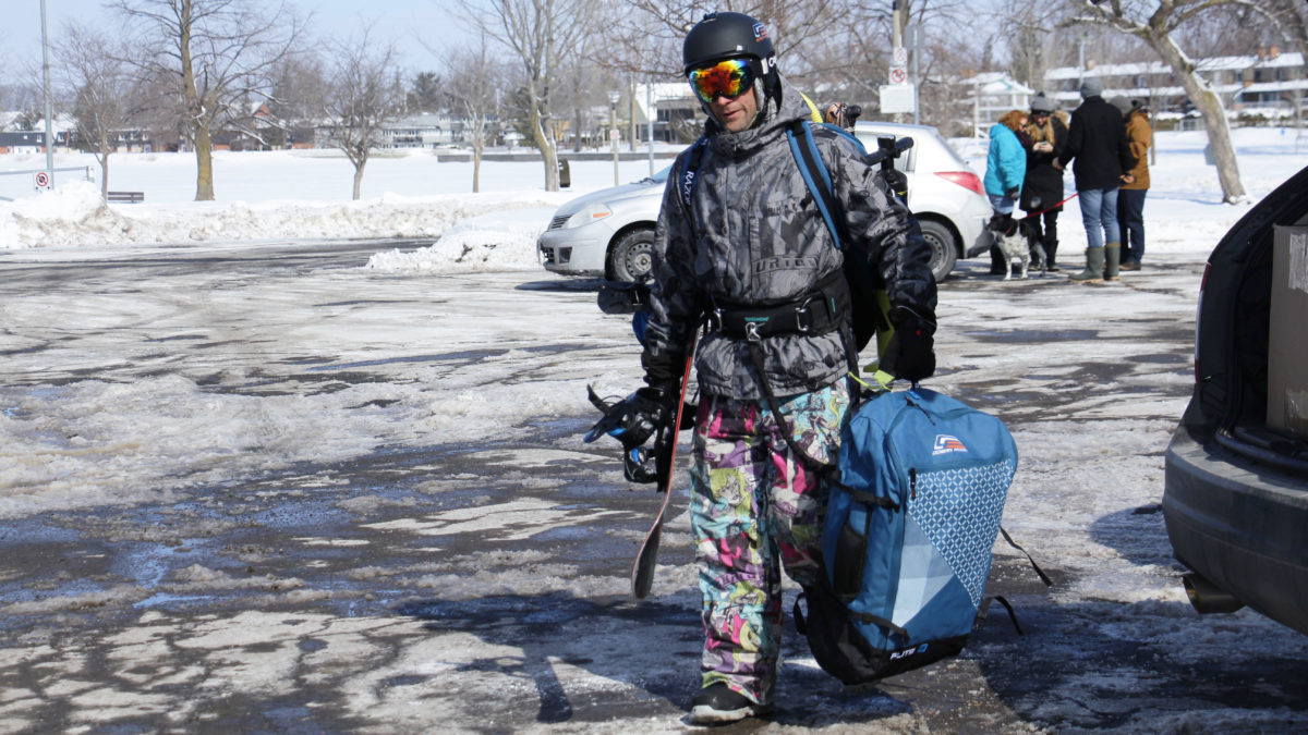 Campbell carries his kiteboarding gear through the parking lot.