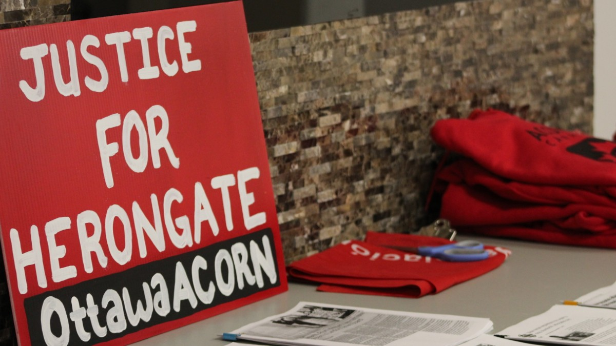 "A sign that reads ""Justice for Heron Gate. Ottawa ACORN,"" placed on a table with shirts and documents at the Community benefits agreement meeting."