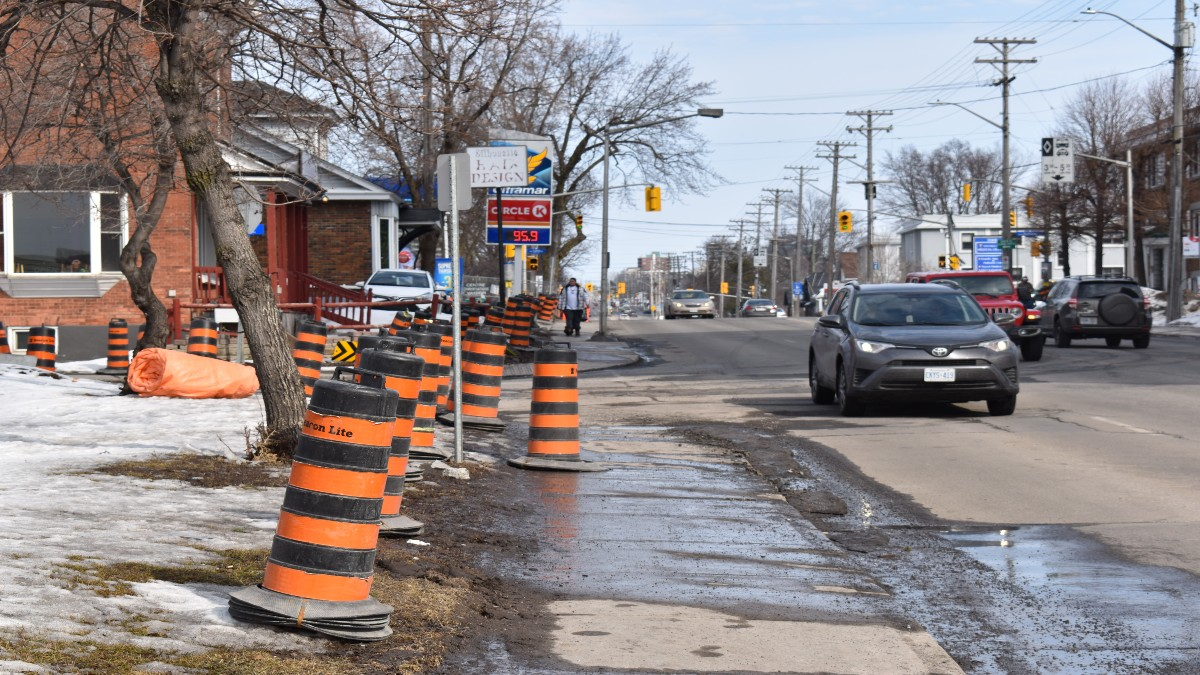 Construction cones placed along the sidewalk on the left side of Montreal Road. A car is driving by.