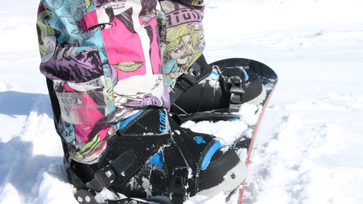 A close up picture of Campbell's pants as he stands on his snowboard