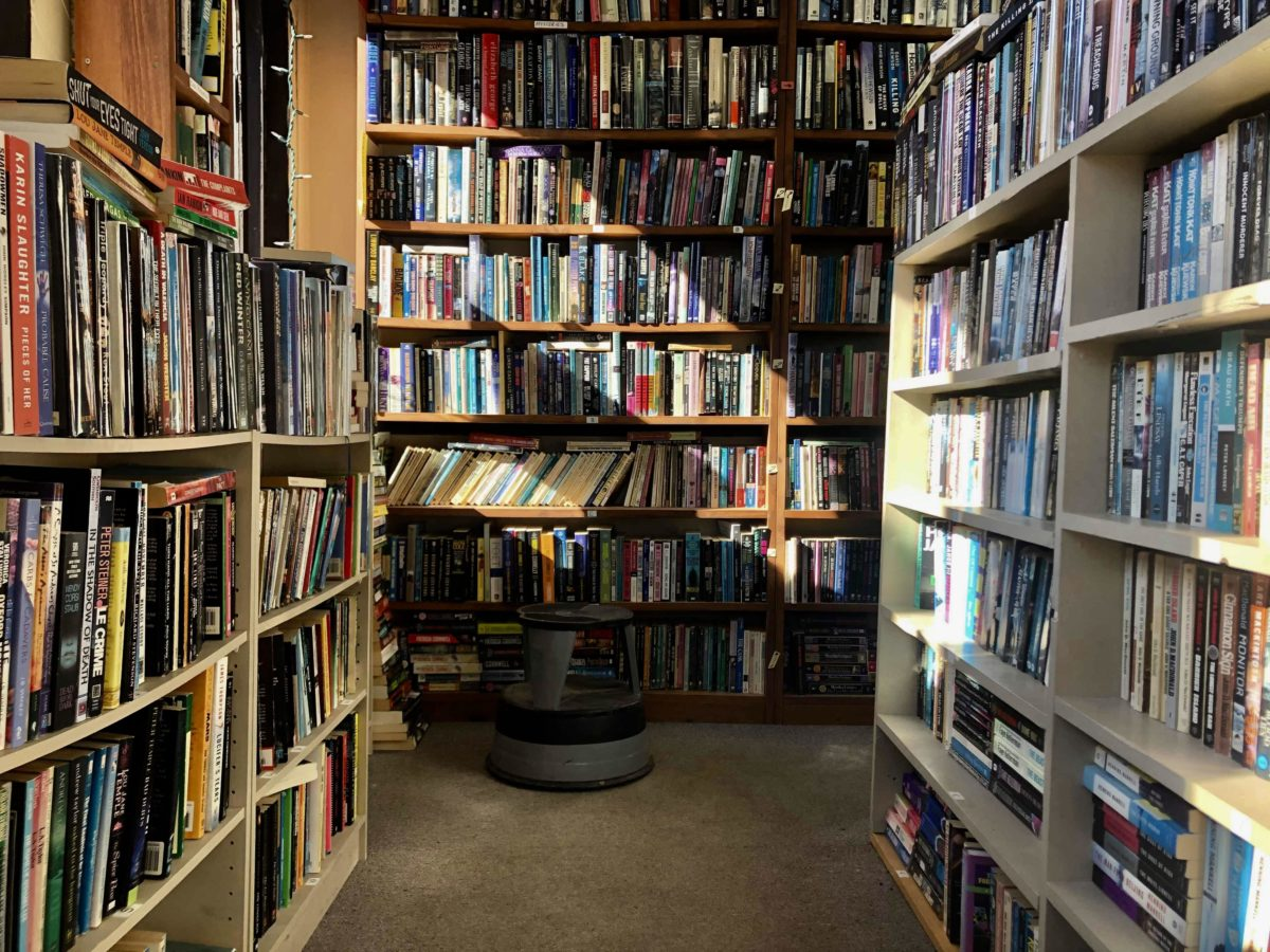 Stacks of books with light shining diagonally across the shelves. Stool in front.