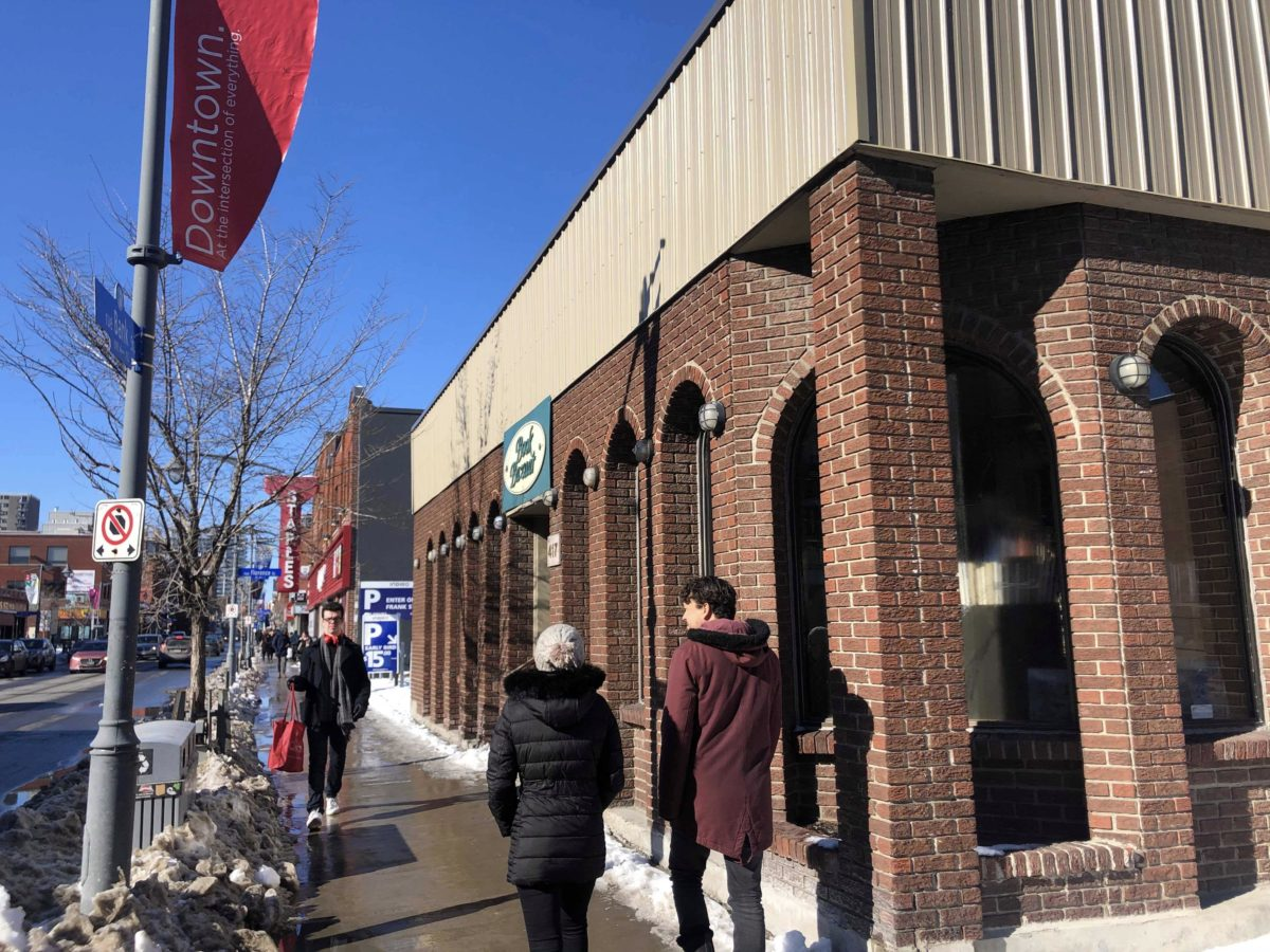 The outside of Book Bazaar. Three people walking by. Snow and slush on sidewalk.