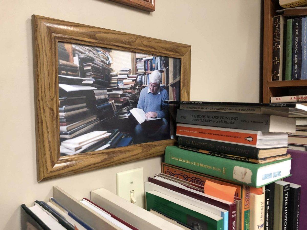 Photo of John Wyatt 30 years ago. Reading a book amongst stacks of other books.