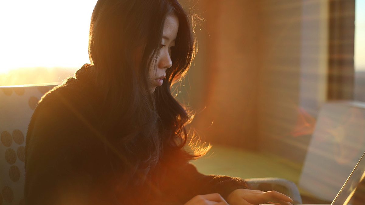 A student sits as she works on her laptop.