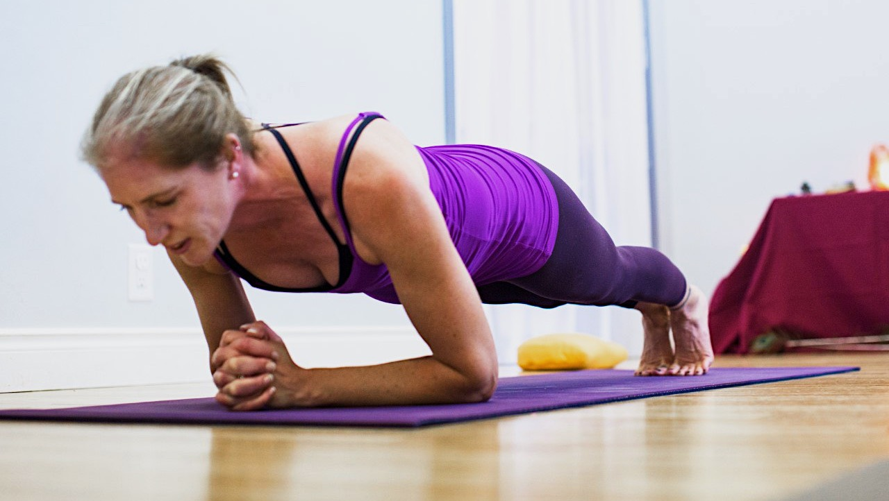 A woman in a purple shirt holds a plank position on a purple yoga matt.