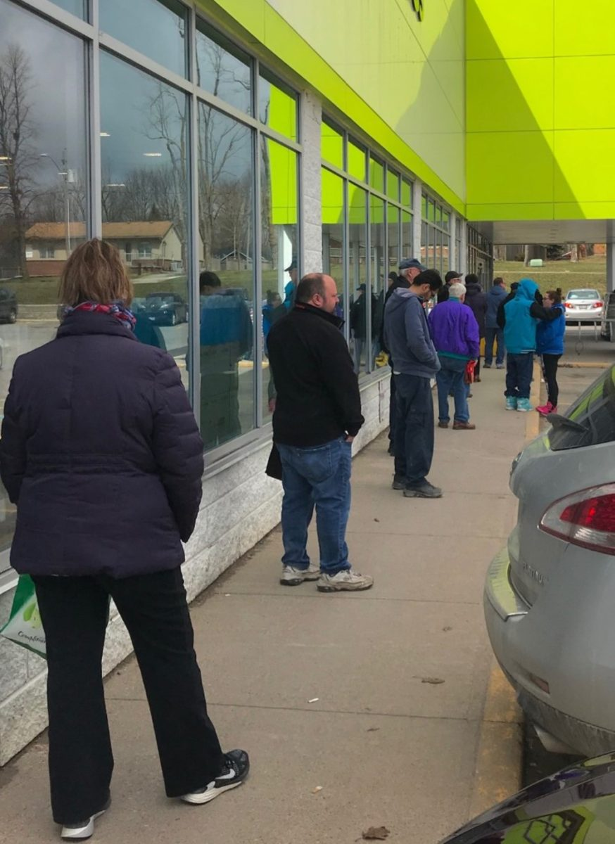 People wait in a long line outside of a grocery store. Each person has about a metre and a half between themselves and anyone around them.