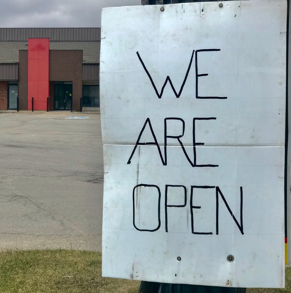 """A handmade sign reads """"we are open"""" in an empty plaza."""