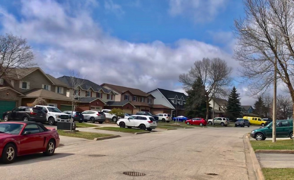 16 cars fill driveways in a suburban neighbourhood.