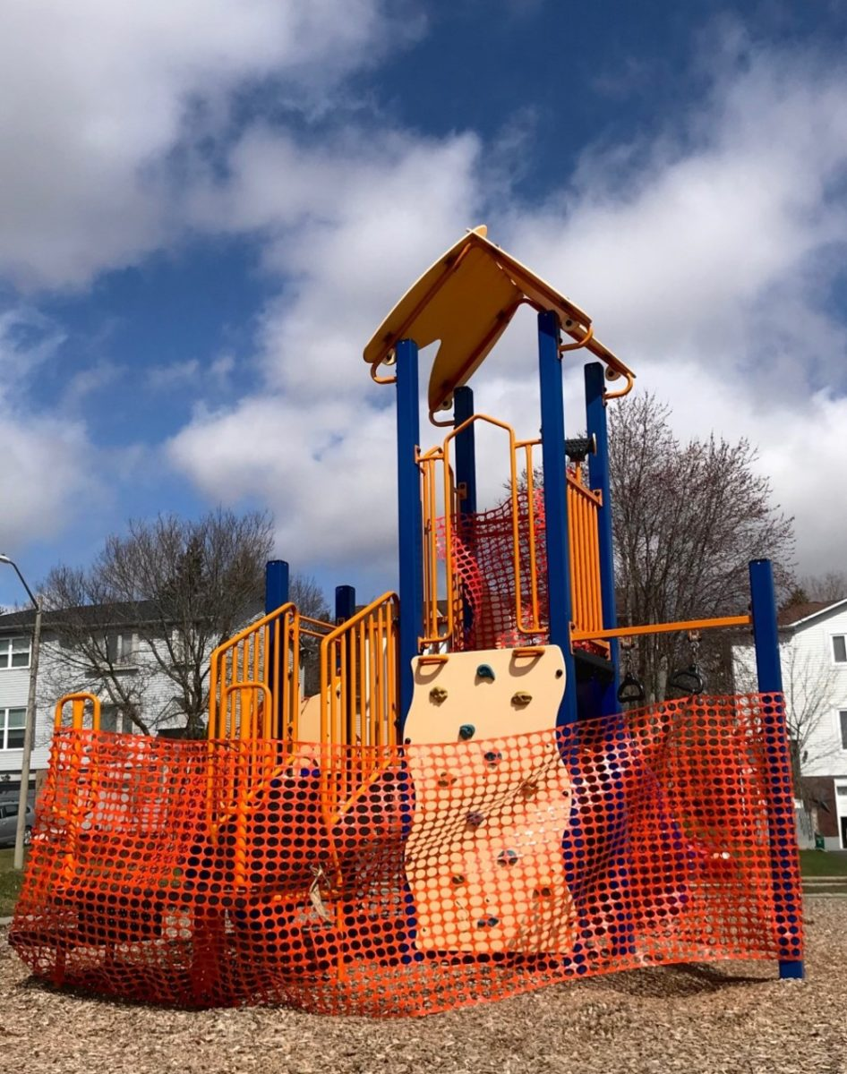 A bright playground is wrapped in plastic wrap to prevent people from climbing on it.