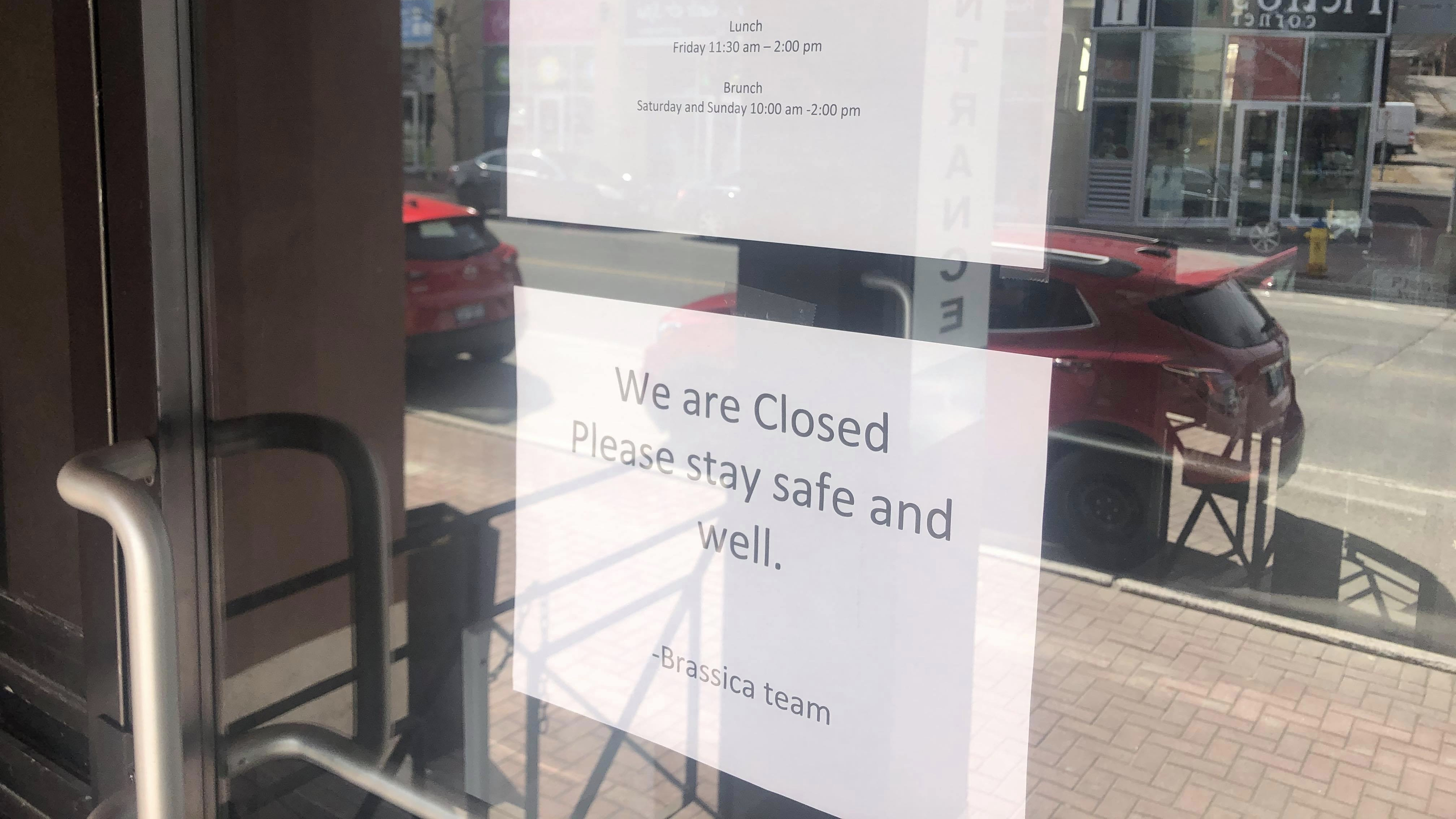 "Front door of Brassica. Notice saying ""We are closed. Please stay safe and well. - Brassica Team."""