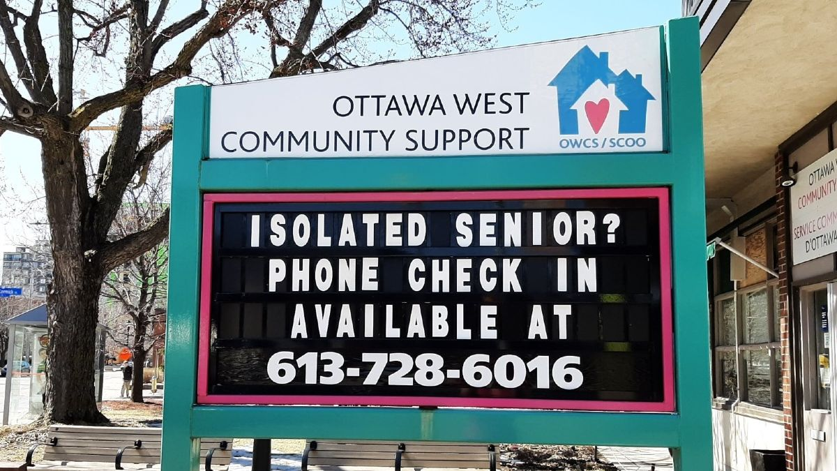 A sign in front of a community centre for seniors gives a phone number for seniors to call if they are isolated during the pandemic.
