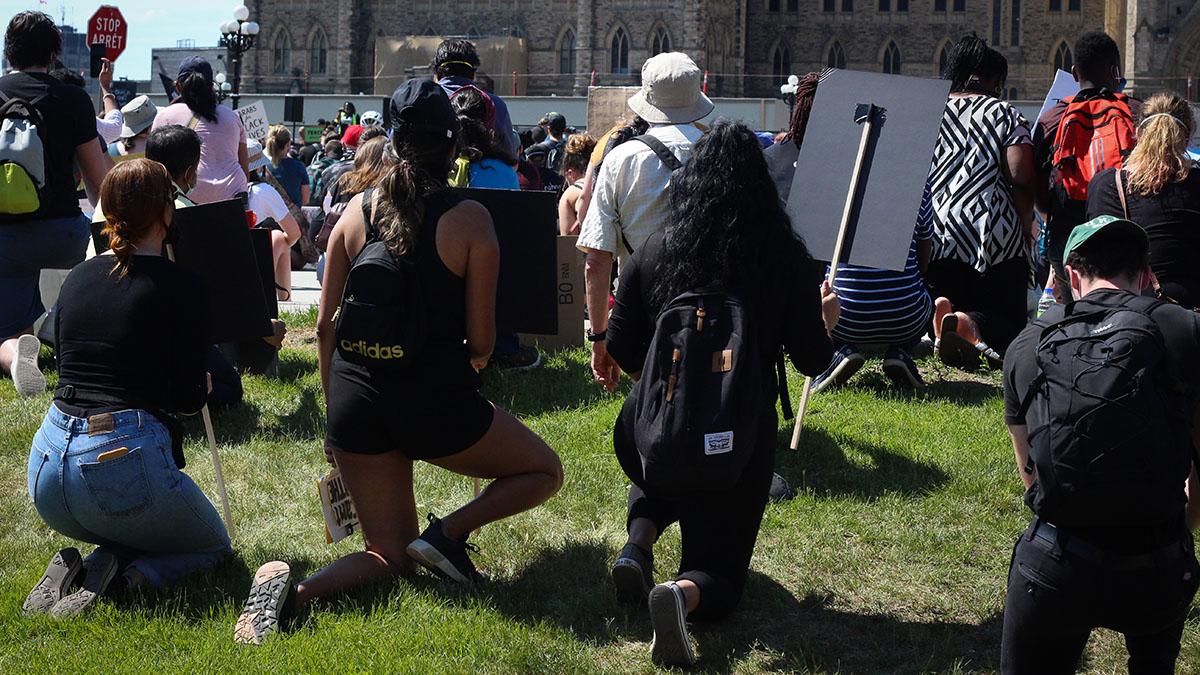 Protestors kneel on Parliament Hill.