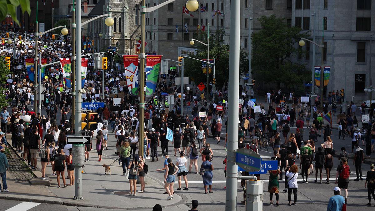 Thousands of protestors walk down Wellington Street.