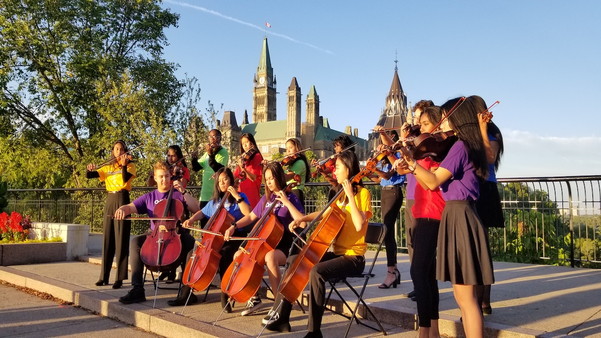 Children from the OrKidstra ensemble play with Parliament Hill in the background