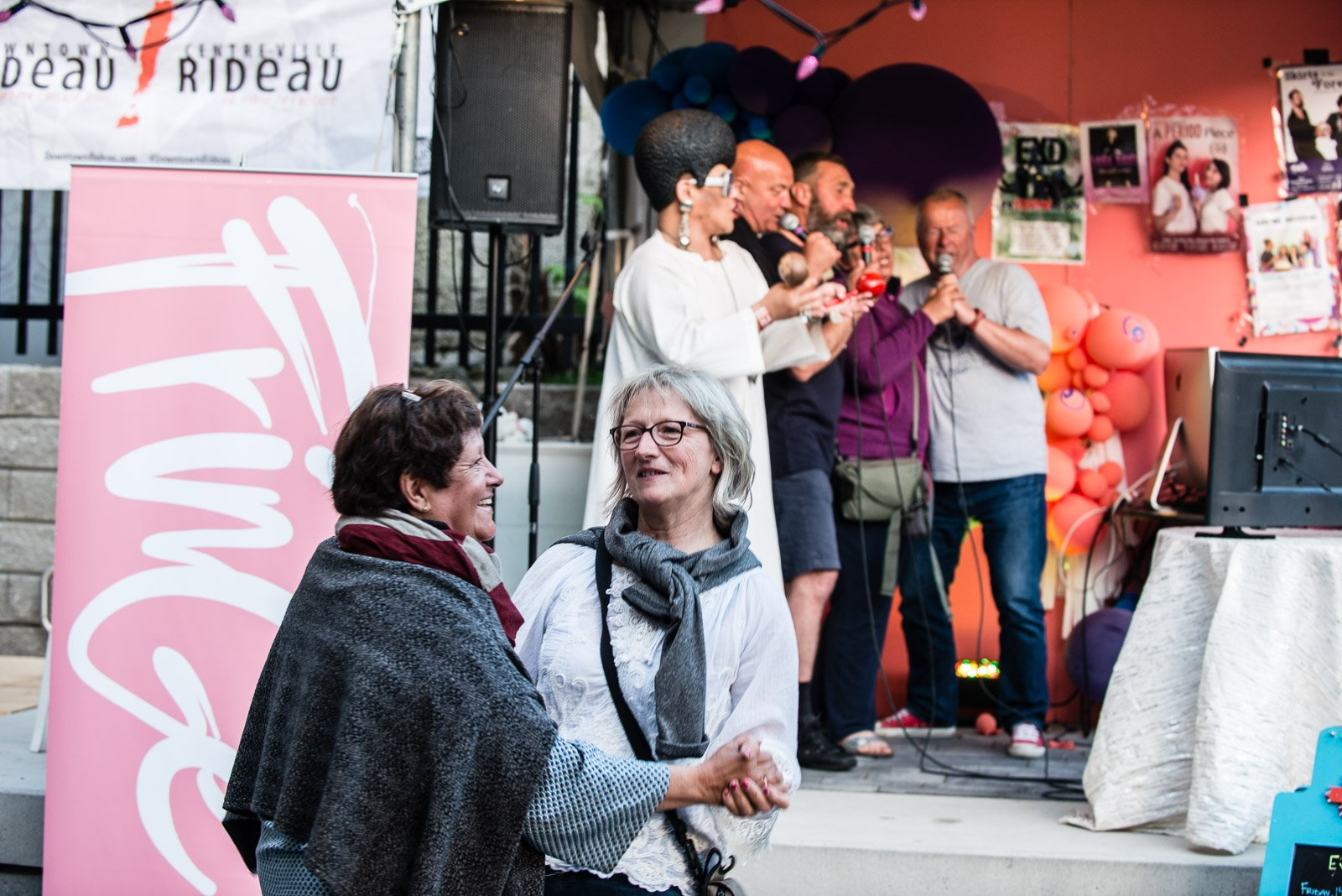 Two festival goers dance together as a group sings karaoke at Ottawa Fringe Festival in 2019.