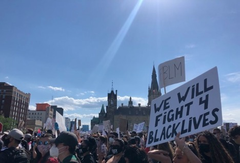 Protestors in masks hold signs in support of Black Lives Matter movement on Parliament Hill.