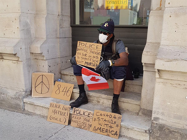 A man sits on steps with protest signs and a Canadian flag.