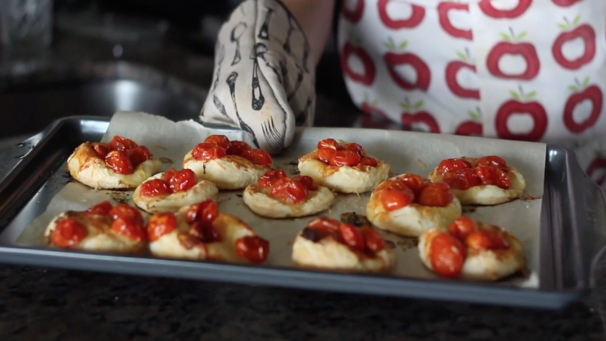 Freshly baked tomato tarts on a cooking tray.
