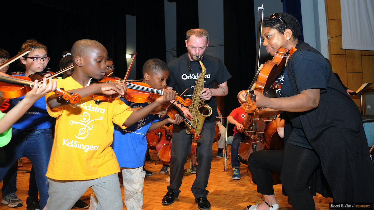 Teaching Artist Kathryn Patricia playing violin with members of the OrKidstra