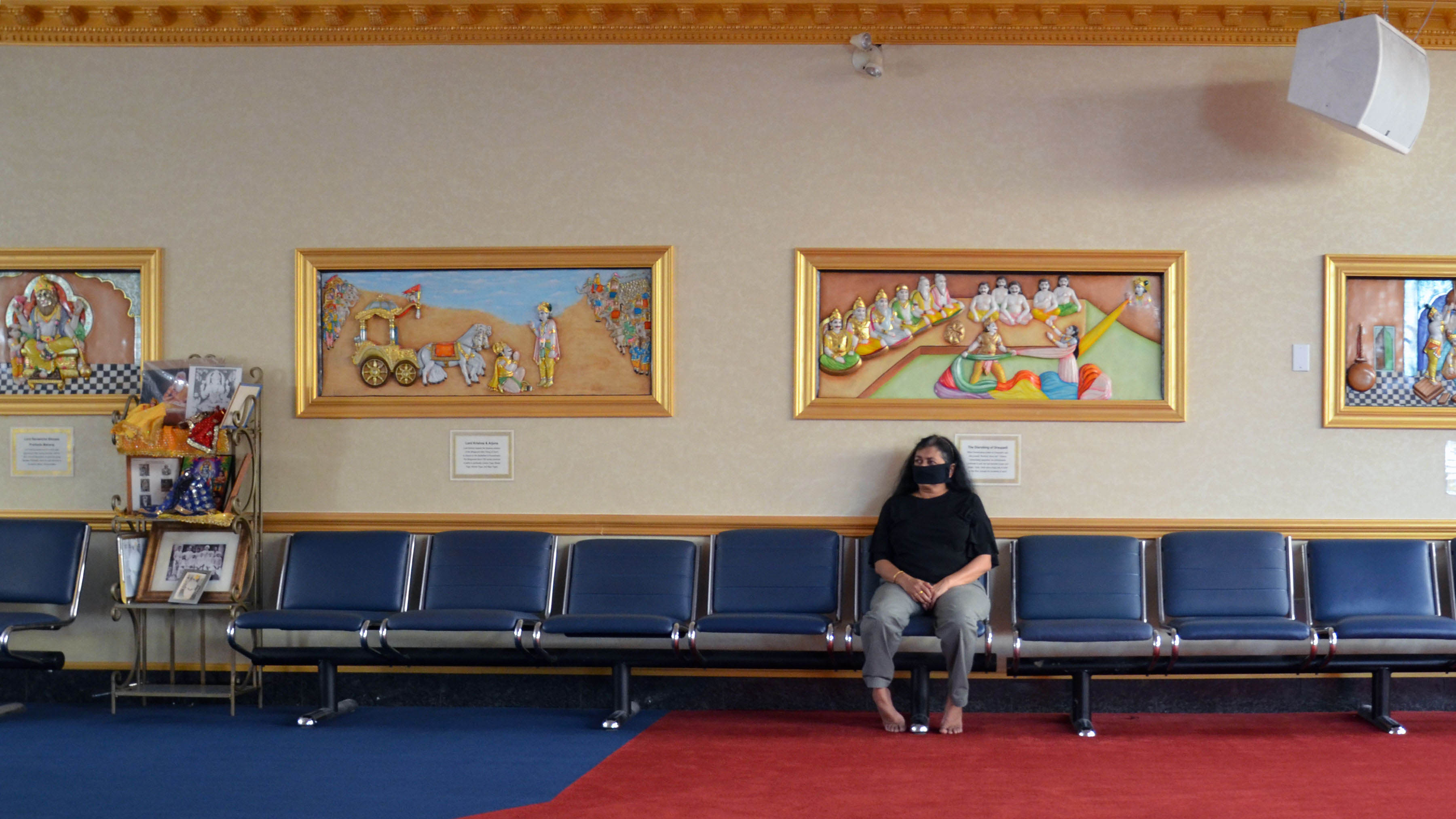 A masked woman sits alone on benches in a Hindu temple.