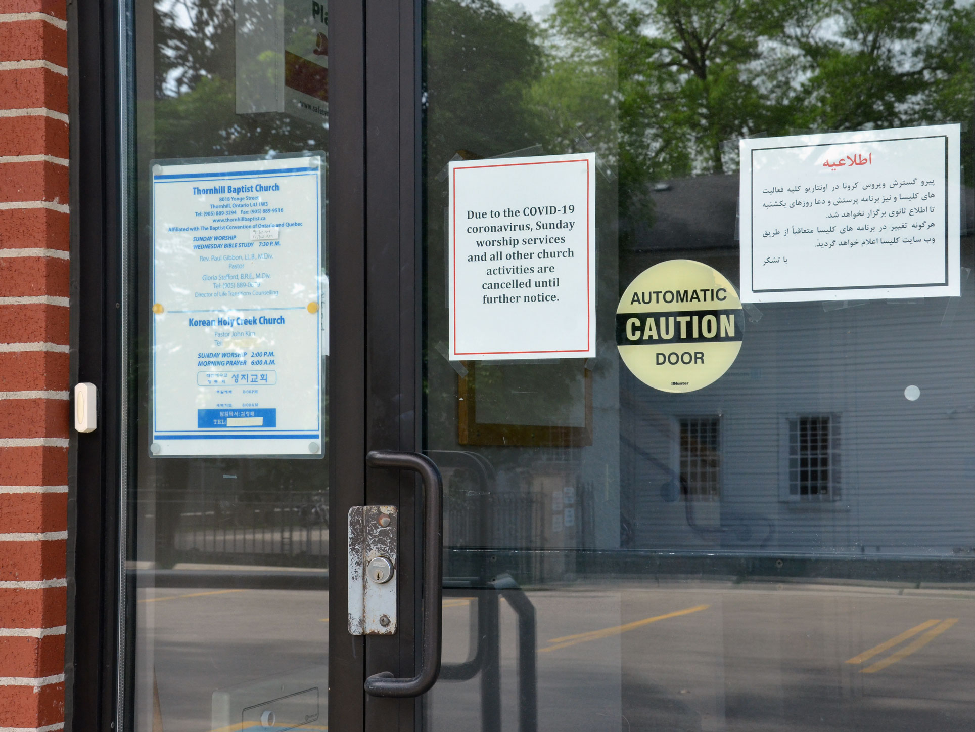 "Amongst three signs on the front door of Thornhill Baptist Church, one  reads ""due to COVID-19 coronavirus, Sunday services and all other church activities are cancelled until further notice."" An empty parking lot is reflected in the door."