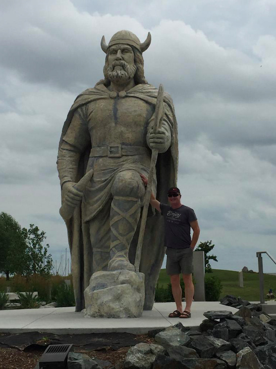 A visitor stands next to the viking statue in Gimli.