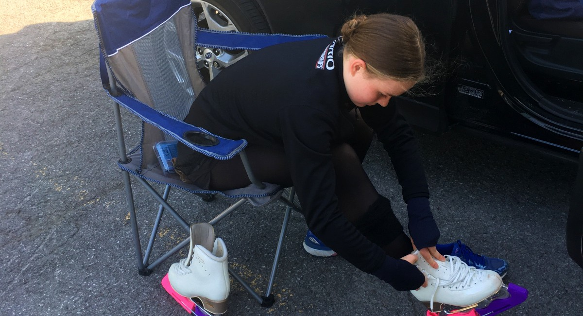 Picture of a figure skater tying up her skates in a parking lot because of COVID-19