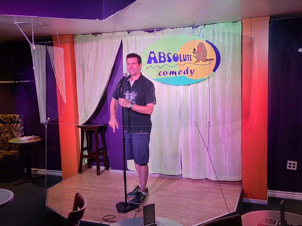 A photo of Jason Laurans, a comedian, performing behind plexiglass at Absolute Comedy.