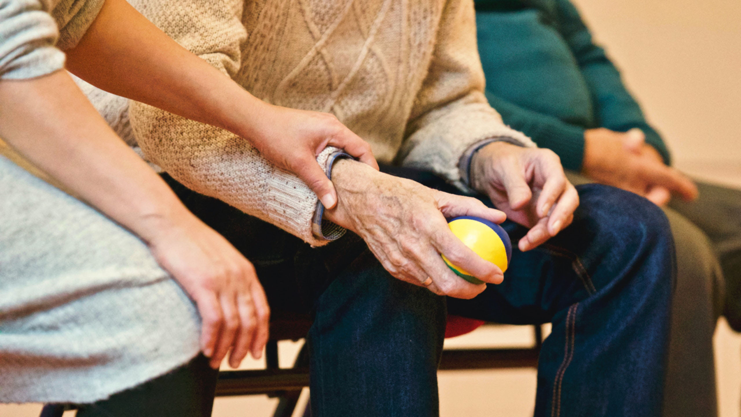 An elderly man holds a stressball.