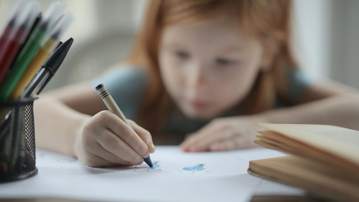 A girl colouring with a crayon.