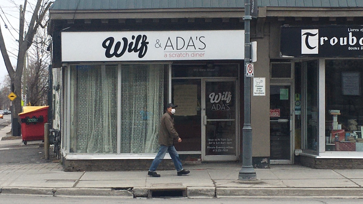A man wearing a mask walks by Wilf & Ada's.