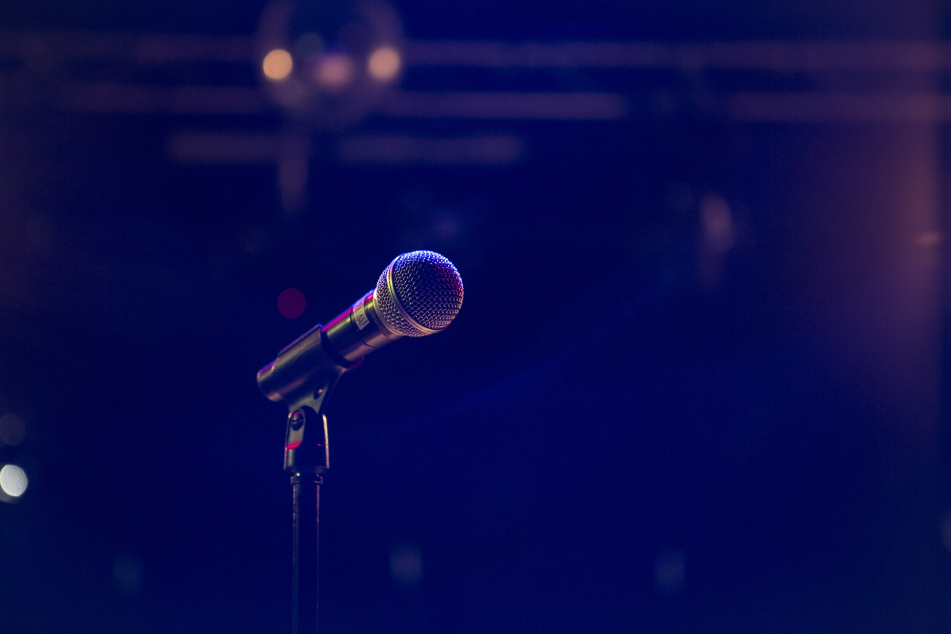 A microphone is pictured against a blurred background.