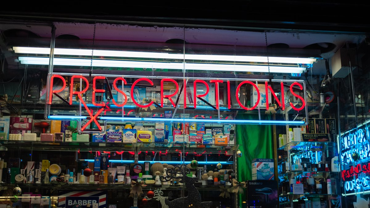 "A red sign in a store reads, ""Prescriptions."" In the background, there are items and medication for sale."