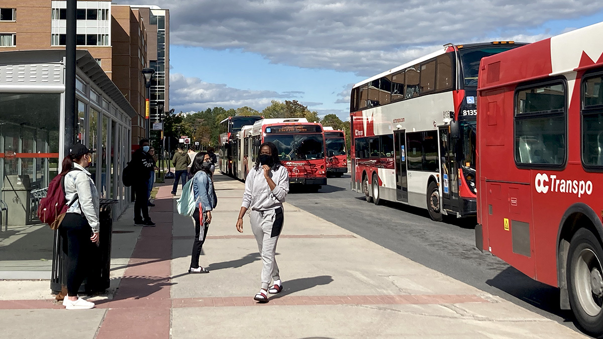 students wearing face coverings wait at the Carleton bus stop