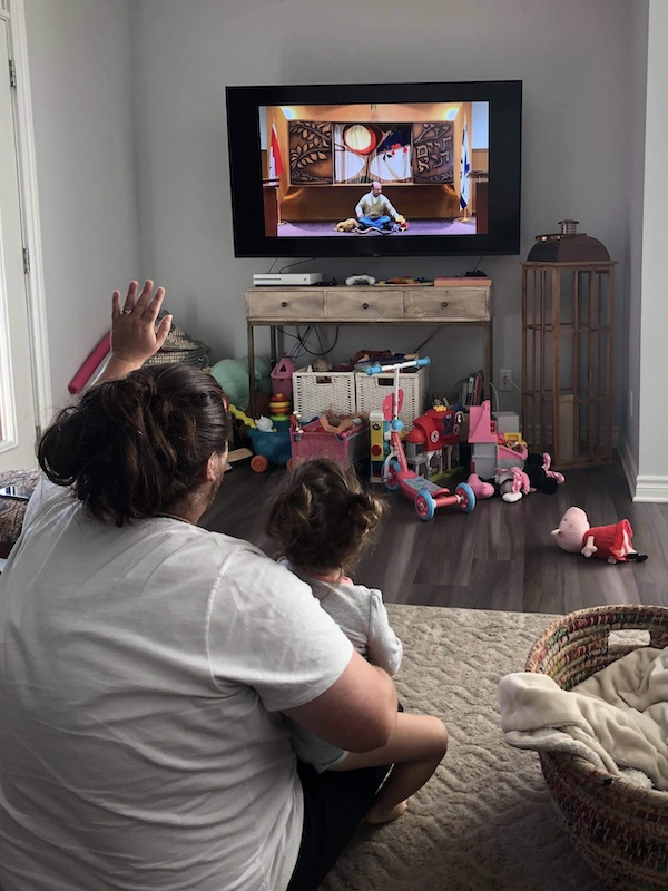 Dad sitting on the floor with daughter in his lap waving at the Television which is screening a Rosh Hashana service of a Rabbi sitting on the floor in front of a Shofar.