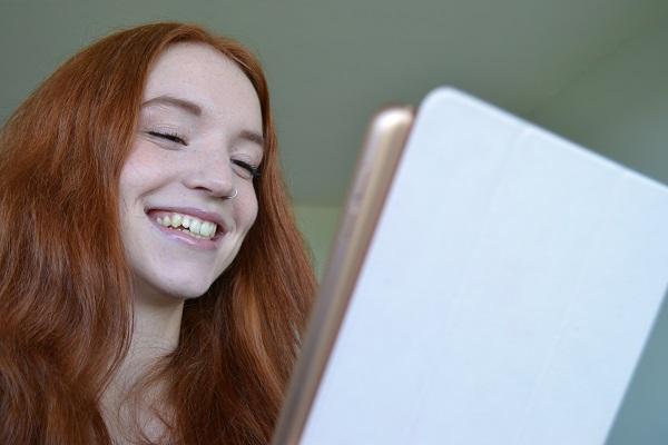 Carleton University student smiling at an iPad.