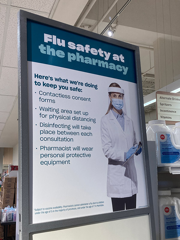 A sign inside a pharmacy that explains what COVID-19 precautions they will be taking, including contactless consent forms, waiting areas for physical distancing, disinfecting and wearing personal protective equipment.